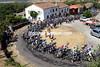 The peloton climbs through a small village near Bejar...