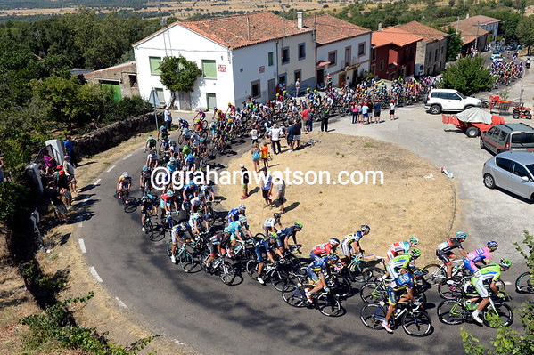 The peloton climbs through a small village near Bejar...