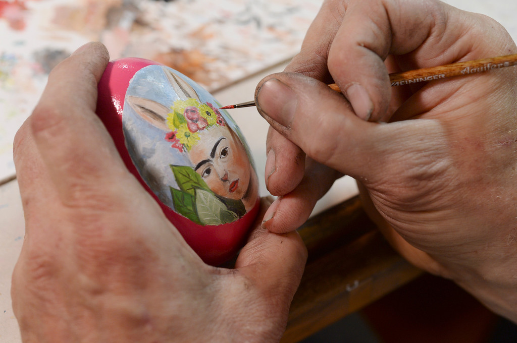 . Dave Thayer used a fine brush to add details to an egg design inspired by Mexican artist Frida Kahlo. Thayer paints a handful of easter eggs each year and adds them to his tree of eggs he puts up in his living room every year. Thayer showed off his artwork to the Denver Post Wednesday, April 2, 2014 at his home in Denver. (Photo by Karl Gehring/The Denver Post)