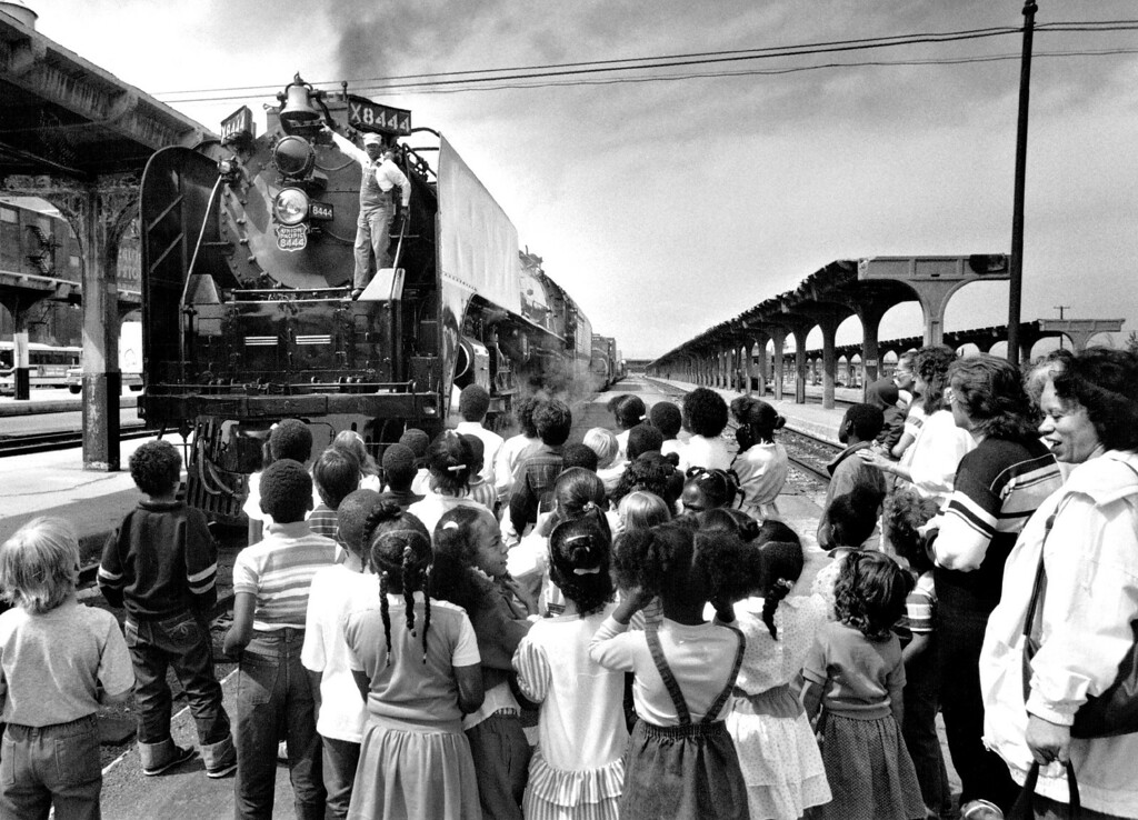 ". First graders and kindergarteners listen to train engineer Fred Perry of Union Pacific talk about the locomotive and also safety, about telling Mom and Dad about being careful when out in the car at a railroad crossing. At Denver Union Station in front of the ""8444 Steam Locomotive\"" in 1988.  (Photo by John Prieto/The Denver Post)"