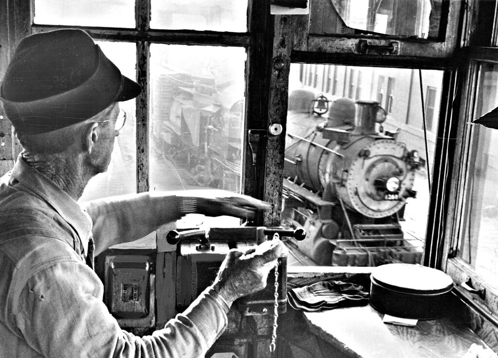 . Sitting in a 4x5-foot tower shack at the 15th St. railway gate station, Edward L. Hogan checks the time on a train puffing through the eight-track crossing. Hogan closes and opens the striped crossing gates 150 times a day, mostly for passing switch engines.  (Photo by Albert Moldvay /The Denver Post)