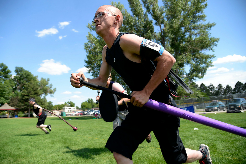. Jess Thompson rushes into battle with his team to gain possession of the jugg. The Colorado Jugger League exhibition and barbecue on Sunday, July 13, 2014. (Photo by AAron Ontiveroz/The Denver Post)