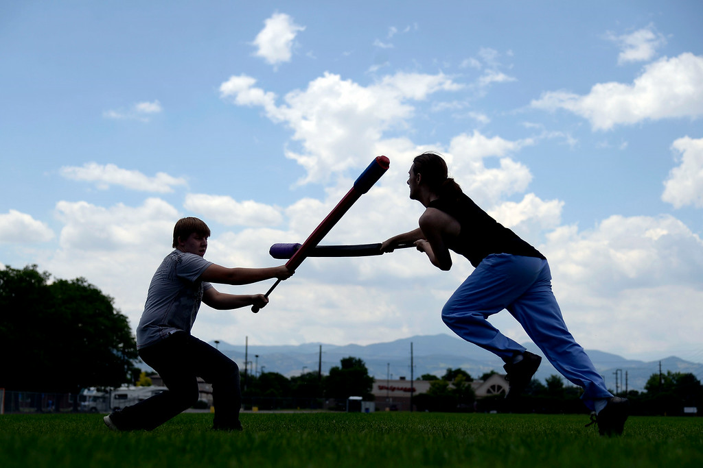 """. Quillen Verner (right) duels Brandon Hajek as they warm up for an exhibition game with an \""""iron man\"""" drill in which one competitor takes on a line of men in successive order until losing. League exhibition and barbecue on Sunday, July 13, 2014. (Photo by AAron Ontiveroz/The Denver Post)"""