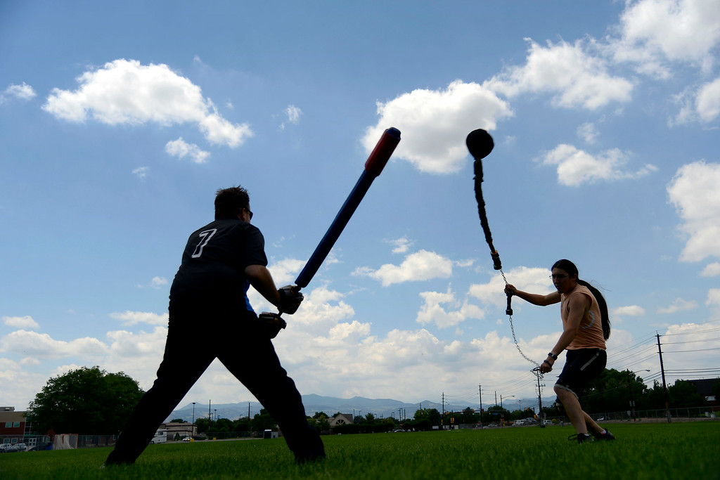 """. Jack Baxter (left) duels Miguel Alvarado as they warm up for an exhibition game with an \""""iron man\"""" drill in which one competitor takes on a line of men in successive order until losing. League exhibition and barbecue on Sunday, July 13, 2014. (Photo by AAron Ontiveroz/The Denver Post)"""