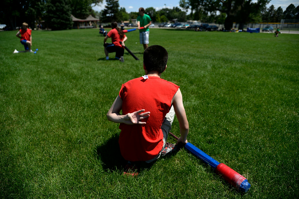 . Jett Salomonman counts drum beats behind his back after being struck. Players who are struck by a sword are down for a five count, while those struck by a ball and chain remain seated for eight counts. The Colorado Jugger League exhibition and barbecue on Sunday, July 13, 2014. (Photo by AAron Ontiveroz/The Denver Post)