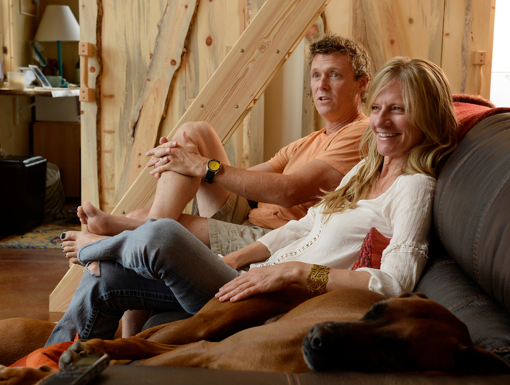 ". David Cottrell and his wife Kristen Moeller in their newly rebuilt home which they rebuilt following the Lower North Fork Fire in 2012. They went from 1200 square feet to 500 square feet. They were at their home which is up Deer Creek Canyon  on Tuesday, July 15, 2014 with one of their 2 dogs, ""Tigger\"" who sleeps on the couch. The couple will be featured in an upcoming episode of Tiny House Nation on FYI network. Moeller is author of the new book, \""What Are You Waiting For? Learn How to Rise to the Occasion Of Your Life.\""   (Denver Post Photo by Cyrus McCrimmon)"