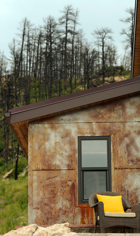 ". David Cottrell and his wife Kristen Moeller have rebuilt their home following the Lower North Fork Fire in 2012. They went from 1200 square feet to 500 square feet. They were at their home which is up Deer Creek Canyon  on Tuesday, July 15, 2014. It has magnificent views but  one can also see five different Colorado forest fire burn zones from past fires from their deck.  The couple will be featured in an upcoming episode of Tiny House Nation on FYI network. Moeller is author of the new book, ""What Are You Waiting For? Learn How to Rise to the Occasion Of Your Life.\""  (Denver Post Photo by Cyrus McCrimmon)"