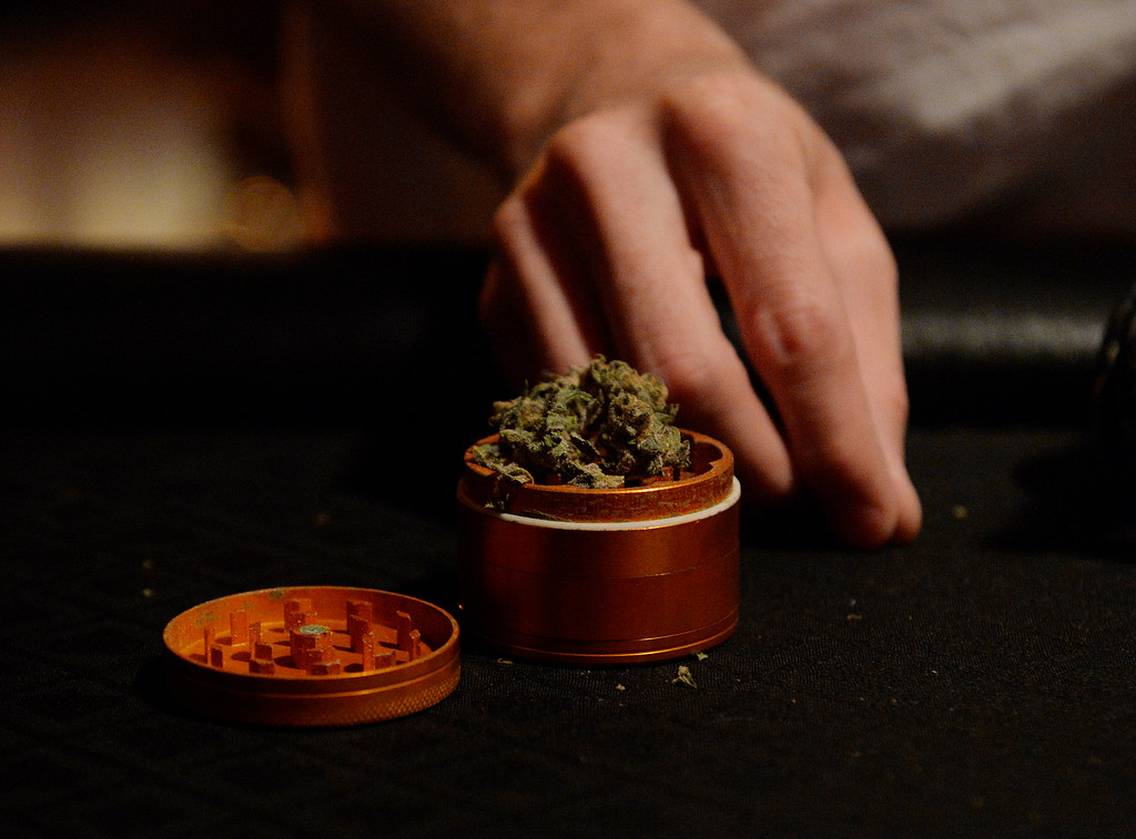 . COLORADO SPRING, CO. - A member stuffs marijuana into a grinder at the Studio A64, a members only cannabis social club, Friday evening, August 15, 2014. (Photo By Andy Cross / The Denver Post)