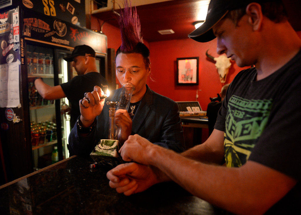 . COLORADO SPRING, CO. - Studio A64 member and musician, Robert Zander, center, lights up a bong hit courtesy of fellow member, Dustin Cooper, right, at the members only cannabis social club, Friday evening, August 15, 2014. (Photo By Andy Cross / The Denver Post)