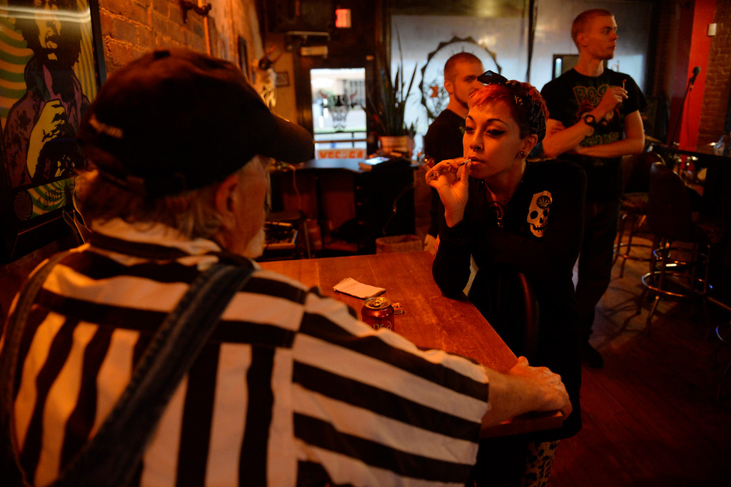 . COLORADO SPRING, CO. - Studio A64, full-time volunteer house server, Janine Choung, smokes a joint with a customer, left, at the members only cannabis social club, Friday evening, August 15, 2014. (Photo By Andy Cross / The Denver Post)