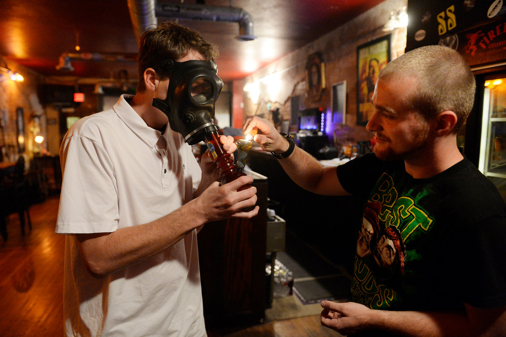 . COLORADO SPRING, CO. - Studio A64 volunteer, Lonnie Terry, right, lights up a gas-mask bong hit for member, Kenny Fields, left, at the members only cannabis social club, Friday evening, August 15, 2014. (Photo By Andy Cross / The Denver Post)