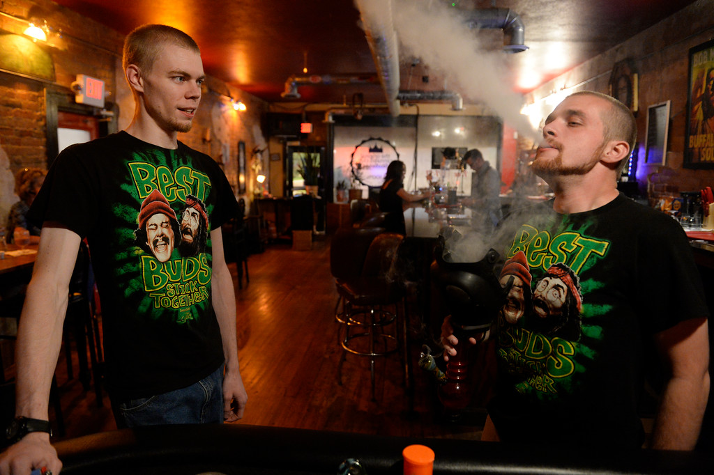 . COLORADO SPRING, CO. - Studio A64 volunteer, Lonnie Terry, right, blows out a huge bong hit as fellow volunteer, Michael Myers, left, waits his turn to take a hit at the members only cannabis social club, Friday evening, August 15, 2014. (Photo By Andy Cross / The Denver Post)