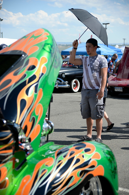 """. A.J. Koon of Denver checks out this 1941 Willys Coupe as more than 13,000 car enthusiasts attend the 10th annual KBPI Rock N Roll car show August 24, 2014 at Bandimere Speedway. There was also a car bash where $1 to take a sledge hammer to a car benefiting \""""US Warriors Outside\"""" providing wooded veterans the opportunity to enjoy their passion for the outdoors. (Photo by John Leyba/The Denver Post)"""