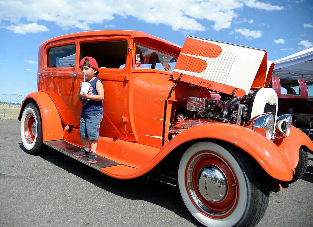 """. Jesiah Martinez 3 years old of Denver takes a sip of his drink as he gets his picture taken with a 1928 Model A  Tudor. More than 13,000 car enthusiasts attend the 10th annual KBPI Rock N Roll car show August 24, 2014 at Bandimere Speedway. There was also a car bash where $1 to take a sledge hammer to a car benefiting \""""US Warriors Outside\"""" providing wooded veterans the opportunity to enjoy their passion for the outdoors. (Photo by John Leyba/The Denver Post)"""