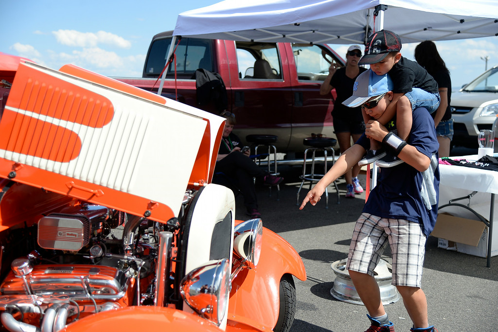 """. Trevor Moonin 12, carries his cousin Cameron Cruz 3 years old as they check out the 1928 Model A Tudor. More than 13,000 car enthusiasts attend the 10th annual KBPI Rock N Roll car show August 24, 2014 at Bandimere Speedway. There was also a car bash where $1 to take a sledge hammer to a car benefiting \""""US Warriors Outside\"""" providing wooded veterans the opportunity to enjoy their passion for the outdoors. (Photo by John Leyba/The Denver Post)"""