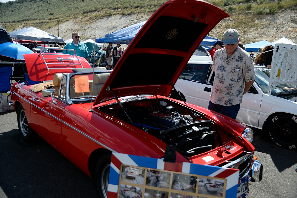 """. Keith Duncan of Thornton checks out this MG as more than 13,000 car enthusiasts attend the 10th annual KBPI Rock N Roll car show August 24, 2014 at Bandimere Speedway. There was also a car bash where $1 to take a sledge hammer to a car benefiting \""""US Warriors Outside\"""" providing wooded veterans the opportunity to enjoy their passion for the outdoors. (Photo by John Leyba/The Denver Post)"""