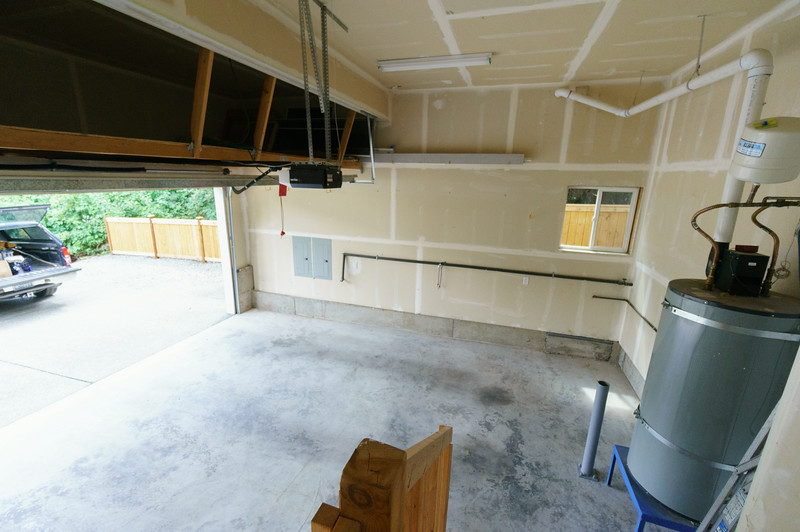 View of garage from door into the house. Storage space above the garage door opener on the left side. There are several stairs to get down into the garage.
