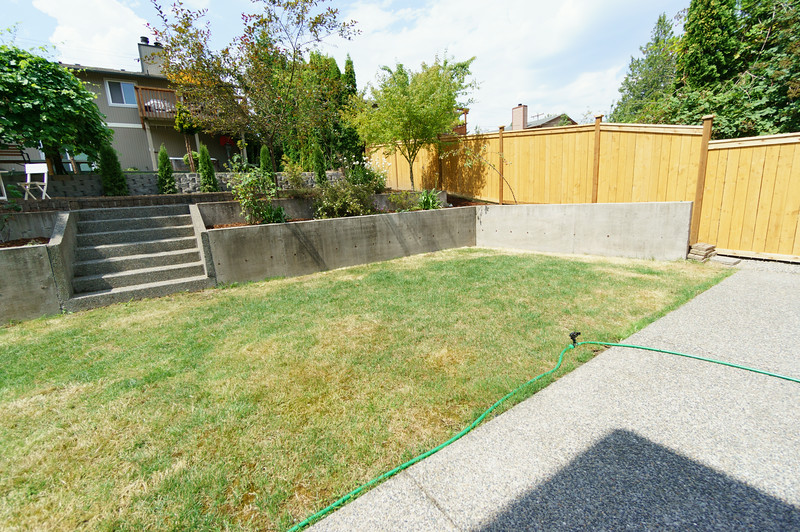 view from sliding door of house into the backyard and to the neighbor's house.
