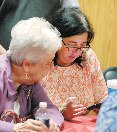 John P. Cleary | The Herald Bulletin<br /> Democratic candidate for Treasurer Kathy Mougeotte, right, checks her phone for results as Martha Carmichael looks on.