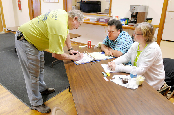 Don Knight | The Herald Bulletin<br /> Lloyd Dixon and Darlene Wilson watch as Bill Jarvis signs in before casting his ballot at the Masonic Lodge in Lapel on Tuesday. Jarvis was the 100th voter to cast his ballot at the precinct.
