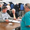 John P. Cleary | The Herald Bulletin<br /> Election clerks Alex Amick and Maxine Ballard check in this voter as the voting booths are full and people are waiting at ward 1, precinct 7 at the National Guard Armory Tuesday.  Poll workers said the turnout had been slow until this bust came about mid-morning.