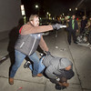 Undercover policeman wards off attackers while trying to arrest rioters. Reuters photo.