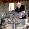 Katie Dahlstrom - kdahlstrom@shawmedia.com<br /> Andrew Collins, a blacksmith apprentice at the the Glidden Homestead's Phineas Vaughan Blacksmith Shop twists a heated piece of steel Sunday. The Glidden Homestead offers blacksmith demonstrations on the second and fourth Sunday of every month through October.