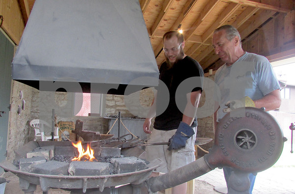 Katie Dahlstrom - kdahlstrom@shawmedia.com<br /> Blacksmith apprentice Andrew Collins and head blacksmith Lucio Bortolin stand near the hearth at the the Glidden Homestead's Phineas Vaughan Blacksmith Shop where they heat pieces of steel to 2,000 degrees before molding them. The Glidden Homestead offers blacksmith demonstrations on the second and fourth Sunday of every month through October.