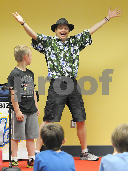 """Ryan Gaines for Shaw Media<br /> At the Sycamore Public Libraries summer reading program kick-off event, entertainer  Jim Cruise, a.k.a. """"Spoon Man"""" performed on Saturday, June 7, 2014 at the library.  Chance Butz, 7, volunteered for one of the portions of the show."""