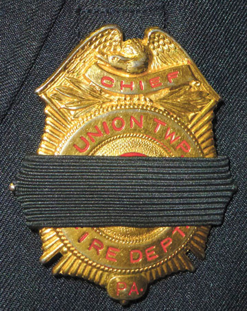 Debbie Wachter/NEWS<br /> The police chief's badge bears the traditional black band denoting the loss of an fellow firefighter.