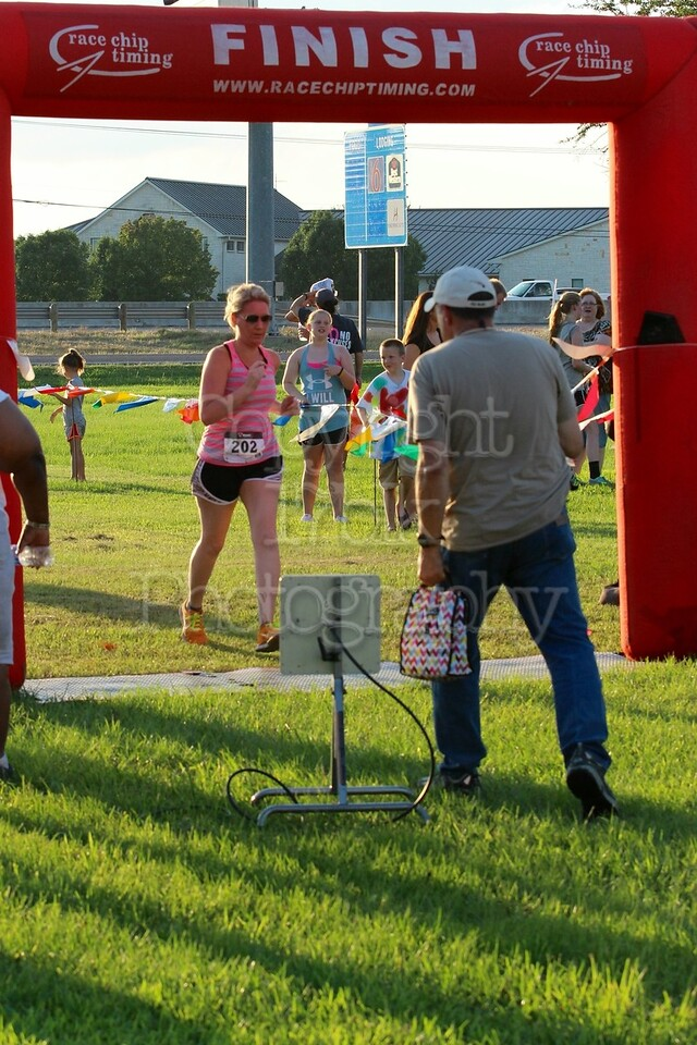 Monica Ames running the 5K Milk Run, crosses the finish line.