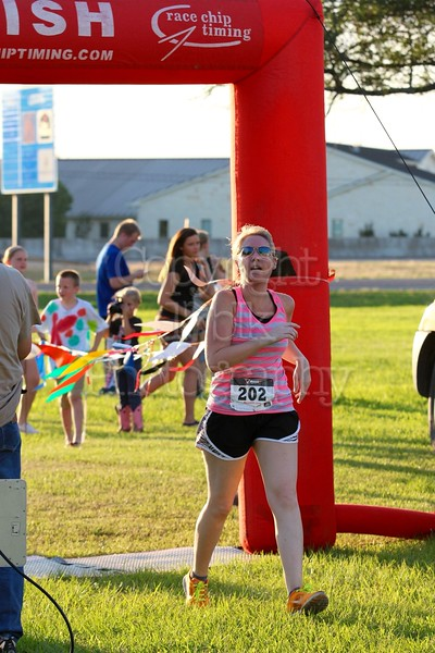 Monica Ames running the 5K Milk Run, crosses the finish line.