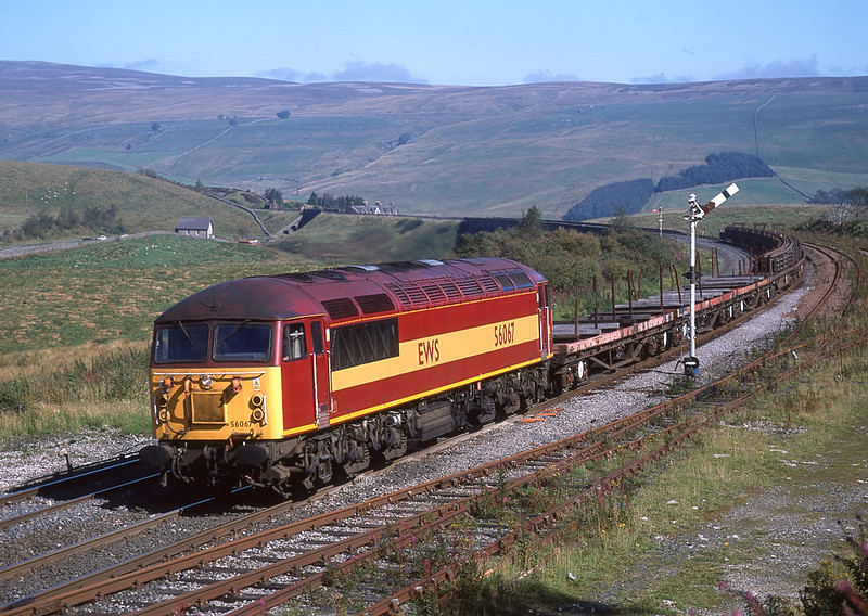 Douglas Johnson collection<br /> <br /> 56067 Rounds the curve passed Garsdale sidings. The class 56 is working 6Z99 Workington to Doncaster Up Decoy train of rails.