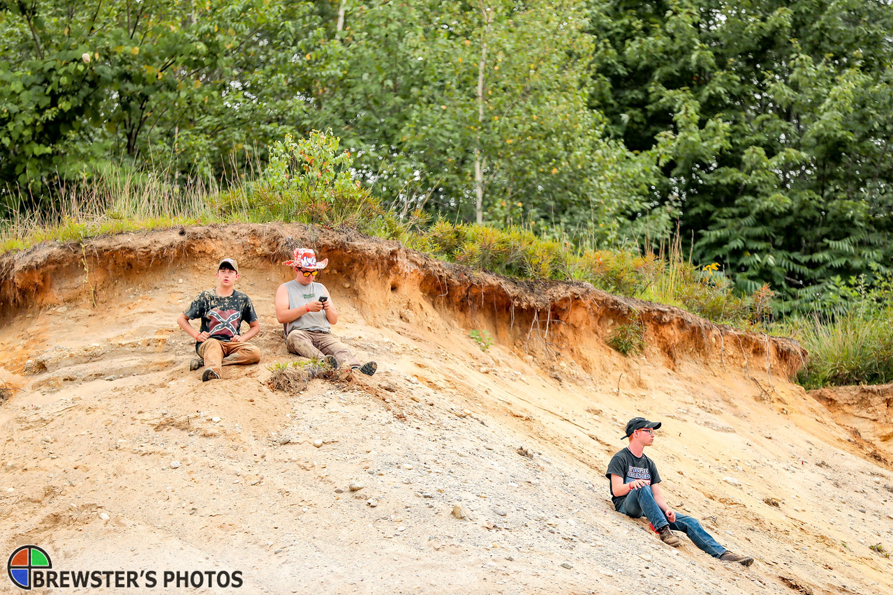 Left to right, Jaiden Jack, Richie and Jesse McMillen watch the games from the top of the gravel pit amphitheater.