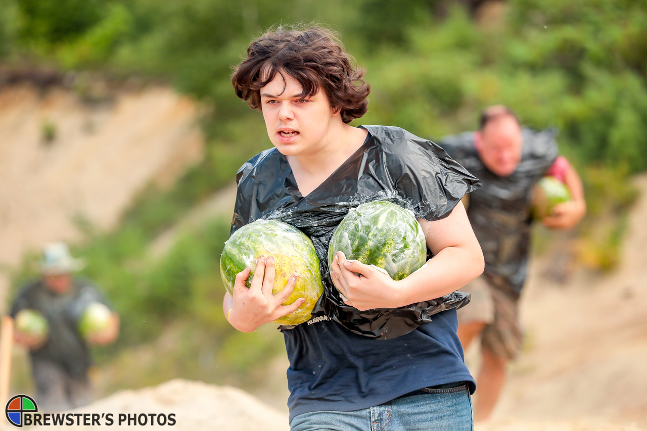Laine Wellington of Warren holds onto his lead and his melons in Greased Melon Carry event yesterday at the Redneck Olympics in Minot.