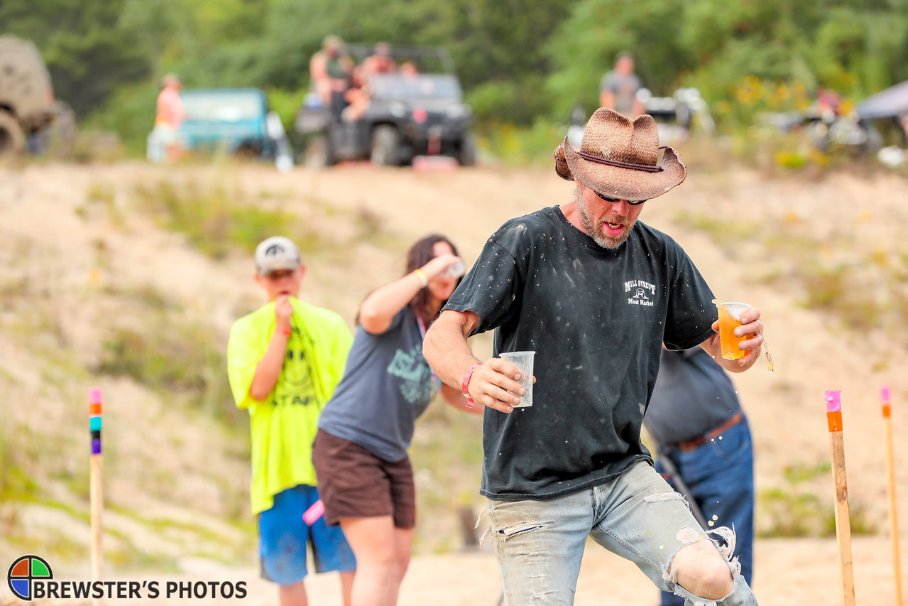A Redneck Olympic staff member demonstrates how to run the beer trot event yesterday at the Redneck Olympics in Minot.