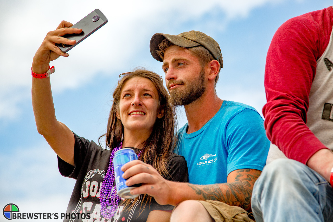 Sitting on a vehicle on the rim of the gravel pit amphitheater, a couple poses for a selfie between events.