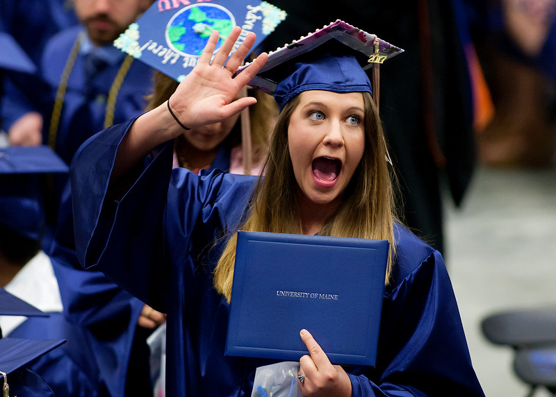 ORONO, Maine -- 05/13/2017 - A graduate holds up her diploma and waves to the crowd during the University of Maine's 215th Commencement at Alfond Arena in Orono Saturday. More than 1,900 students, including 34 doctoral degree candidates, were expected to participate in the two commencement ceremonies. Ashley L. Conti | BDN