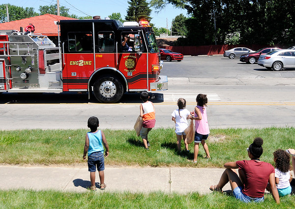 Don Knight | The Herald Bulletin<br /> Firefighters toss candy from Engine 2 to kids waiting on the sidewalk during the Anderson Black Expo parade on Saturday.
