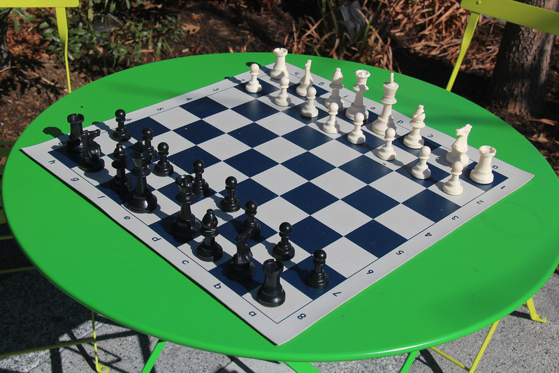 There are yellow and green tables & chairs throughout the park.  A chessboard was set up on this table.