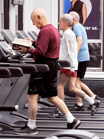 John P. Cleary | The Herald Bulletin<br /> These men get their morning workout on the treadmill at the Anderson YMCA with one gentleman catching up on his reading while he walks.