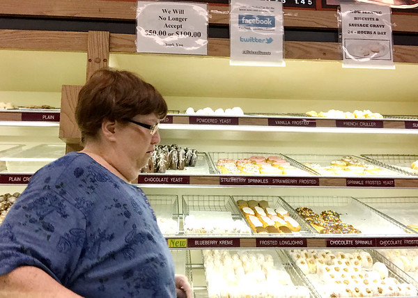 Megan Adams stand guard over the doughnuts at Deluxe Donuts on Scatterfield Road.