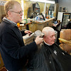 John P. Cleary | The Herald Bulletin<br /> Butch Harris gets his hair cut by Mick Cox, proprietor of the Barber Shop at 23rd and Main Street. Harris has been getting trimmed here since 1962 with Cox wielding the scissors for the past 20 years.