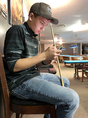 Cole Peavler, 14, checks his phone while waiting for his shot at The Billiard Club on East Seventh Street.