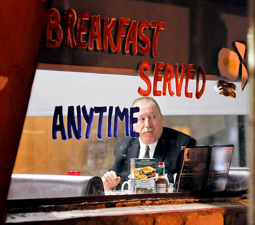 John P. Cleary | The Herald Bulletin<br /> Anderson Police Department assistant chief Mark Cole glances out the window at the rain as he has his early morning breakfast.