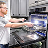 Don Knight | The Herald Bulletin<br /> Chris Wedekind pulls a Mexican chicken casserole from the oven as the family prepares for dinner.
