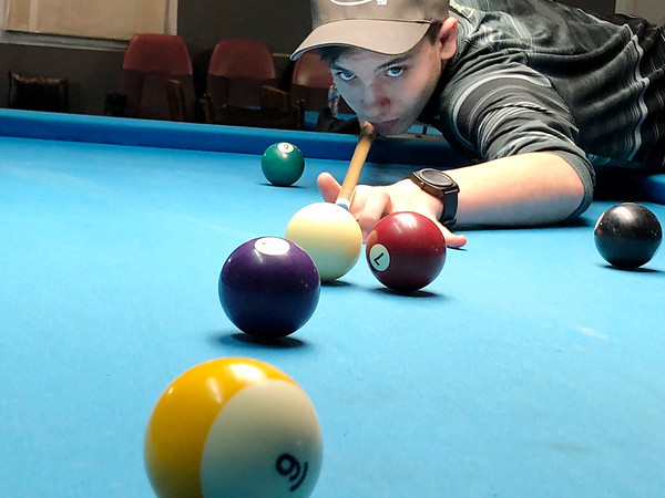 Cole Peavler, 14, takes a shot at The Billiard Club on East Seventh Street.