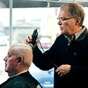 John P. Cleary | The Herald Bulletin<br /> Butch Harris gets his hair cut by Mick Cox, proprietor of the Barber Shop at 23rd and Main Street.