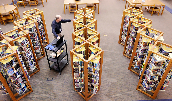 John P. Cleary | The Herald Bulletin<br /> Bob Wood, APL's homebound delivery clerk, goes through the racks of paperback books this morning picking out selections for homebound clients to deliver this day.