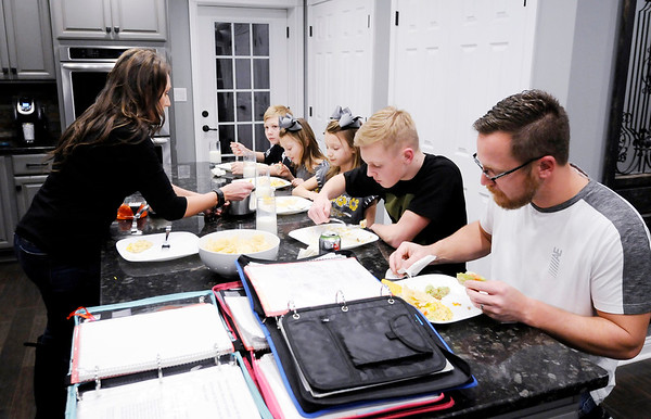 Don Knight | The Herald Bulletin<br /> Shannon Wedekind spoons out cheese dip while looking over her childrens' binders making sure they are ready for the next day.
